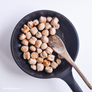 chopped sausage in a black skillet with wooden spoon