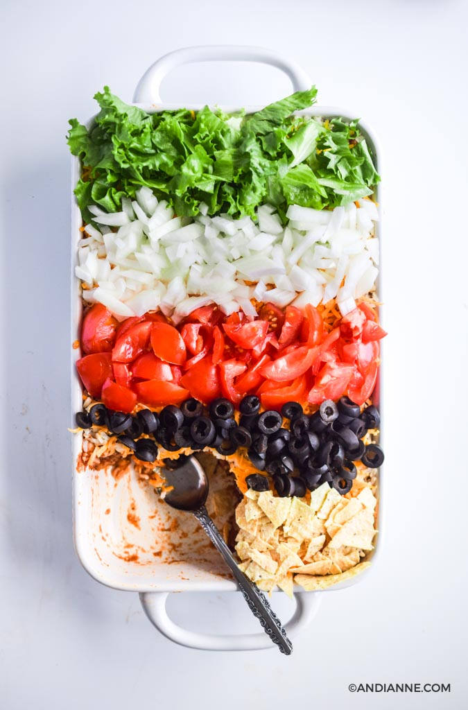 taco salad casserole with stripes of fresh vegetables and crushed nacho chips on top to create a rainbow effect. Once serving has been taken out of the bottom left corner. A silver spoon is in its place.