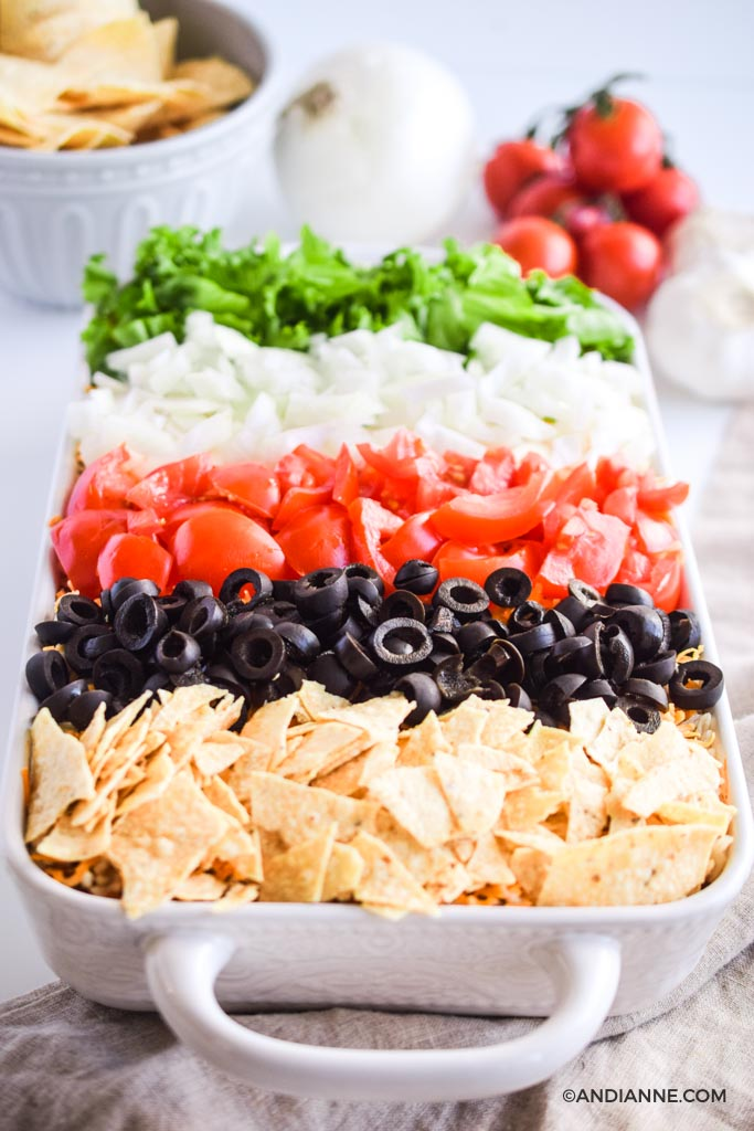 angled close up of taco casserole recipe in white dish with stripes of crushed nachos, sliced olives, sliced tomatoes, sliced onion, and chopped lettuce are on top.