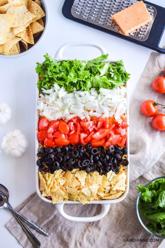 taco salad casserole with stripes of fresh vegetables and crushed nacho chips on top to create a rainbow effect. A cheese grater, bowl of nacho chips, fresh tomatoes, garlic bulbs and spoons all surround the casserole dish.
