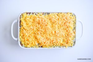 shredded cheddar cheese layer on top of white casserole dish