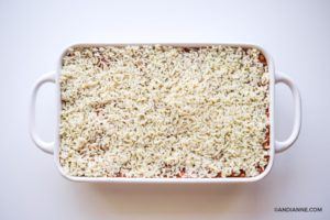 rice on top of ground beef mixture in white casserole dish