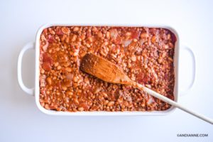 ground beef mixture in white casserole dish. Wooden spoon on top