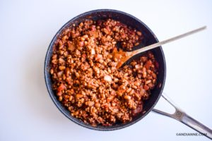 ground beef and tomato mixture in black skillet with wooden spoon