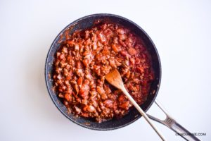 ground beef and tomato sauce in black skillet with wooden spoon