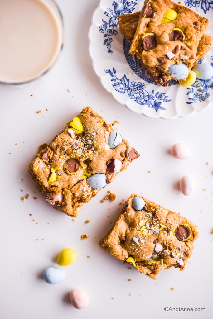 mini egg cookie bars cut out with small white and blue plate and glass of milk on white counter