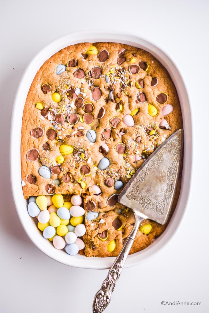 easter egg blondies cooked in white oval dish with silver pie cutter on top and cadbury mini eggs poured into cut out piece in bottom left