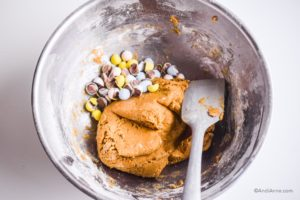 batter in large silver bowl with silicone spatula and crushed cadbury mini eggs beside batter
