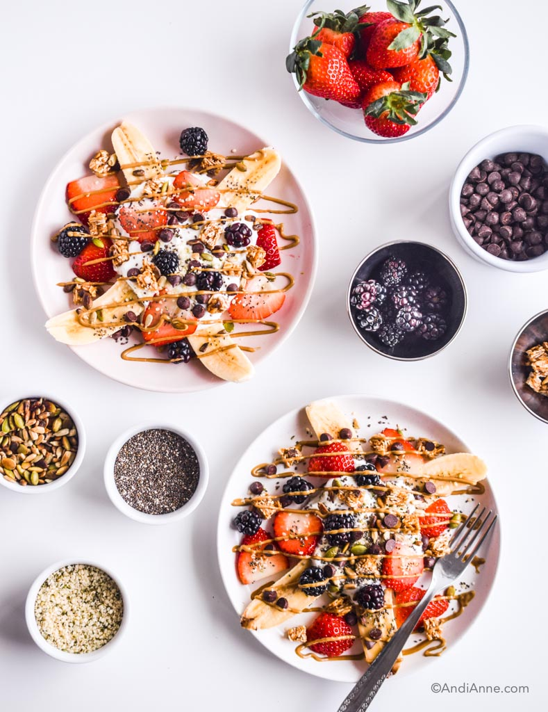 healthy banana splits on pink plates with a fork. small bowls of ingredients around the plates including white bols of pumpkin seeds, hemp seeds, chia seeds and chocolate chips.