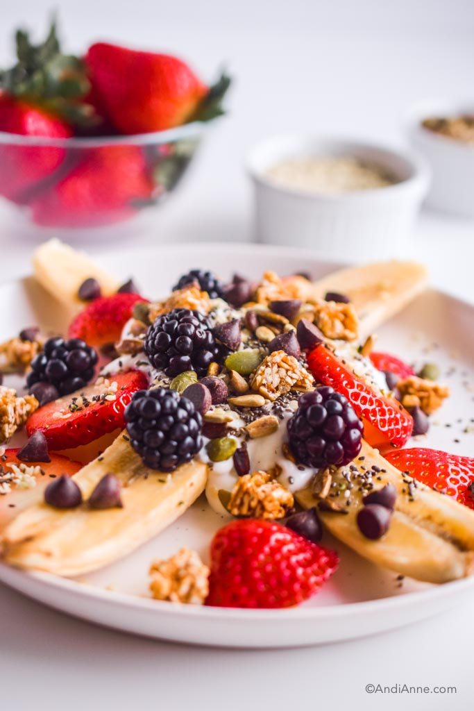 Close up detail of healthy banana split. Details of blackberries, pumpkin seeds, chocolate chips and granola can be seen.