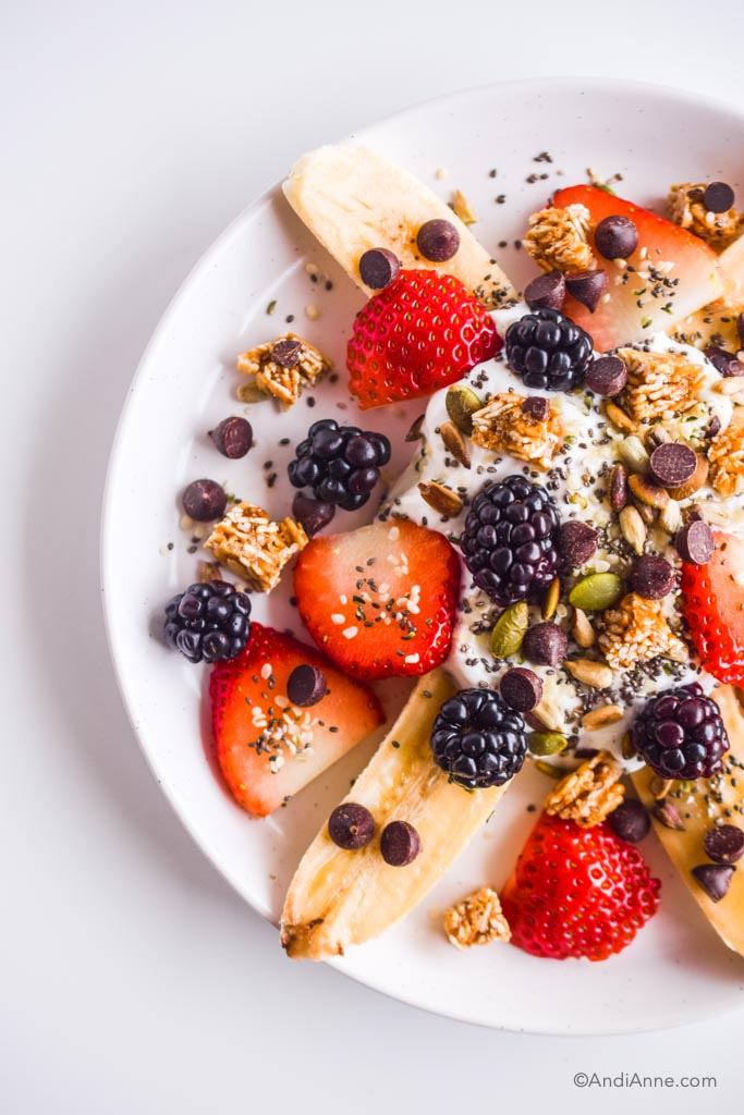 Detail of healthy banana split on white plate with strawberries, blackberries, seeds, and chocolate chips.