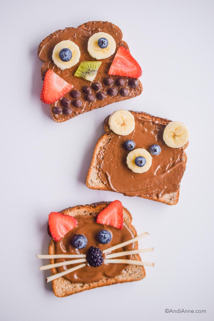 3 animal designed toasts with brown nut butter and fruit to design animal shapes on top