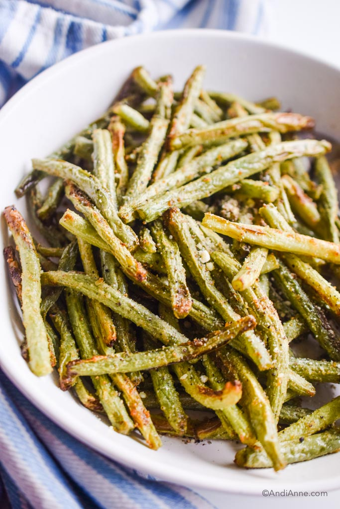 air fryer green beans in a white bowl with striped napkin around it