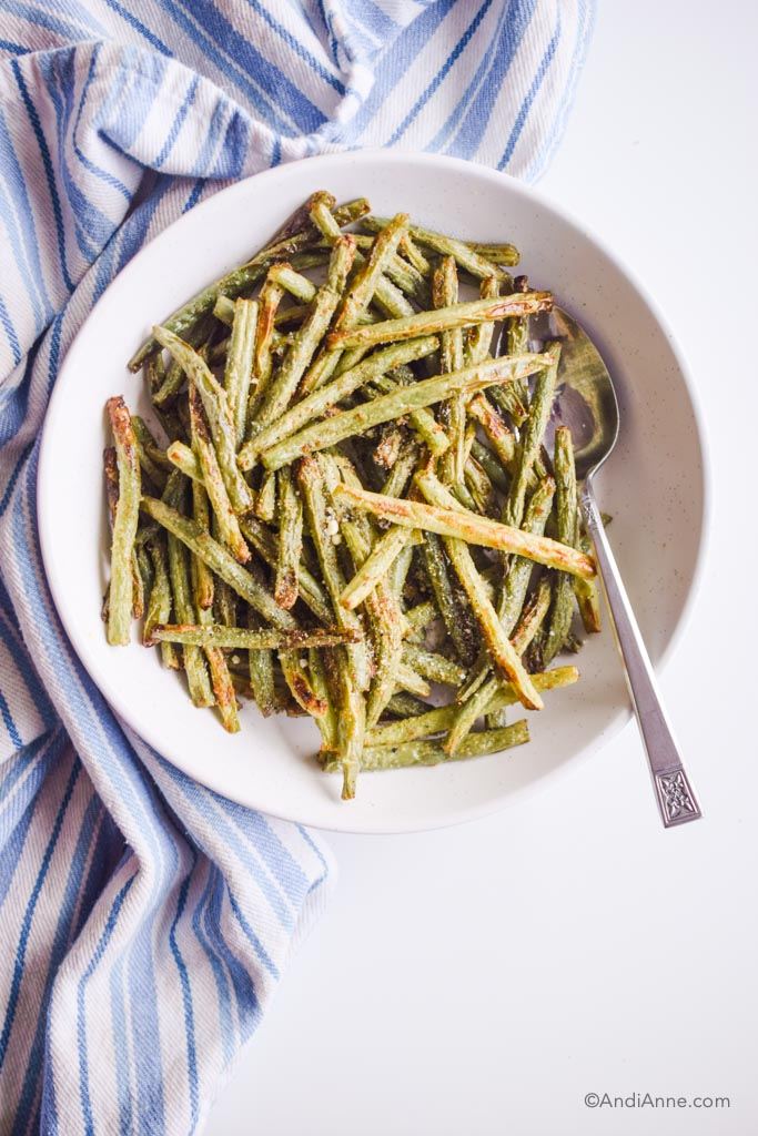 cooked air fryer green beans in white bowl with silver spoon and striped napkin