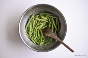 green beans tossed with dressing in a large metal bowl with wooden spoon