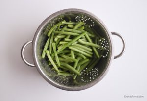 sliced green beans in a metal strainer