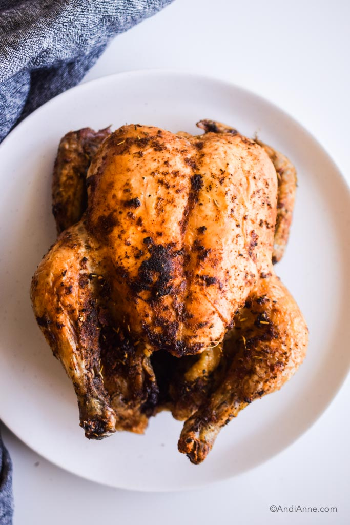 air fryer whole chicken cooked on a white plate