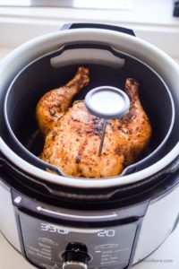 meat thermometer poked into chicken breast of chicken in an air fryer