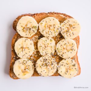 nut butter spread on toast with sliced bananas, hemp seeds and chia seeds on top