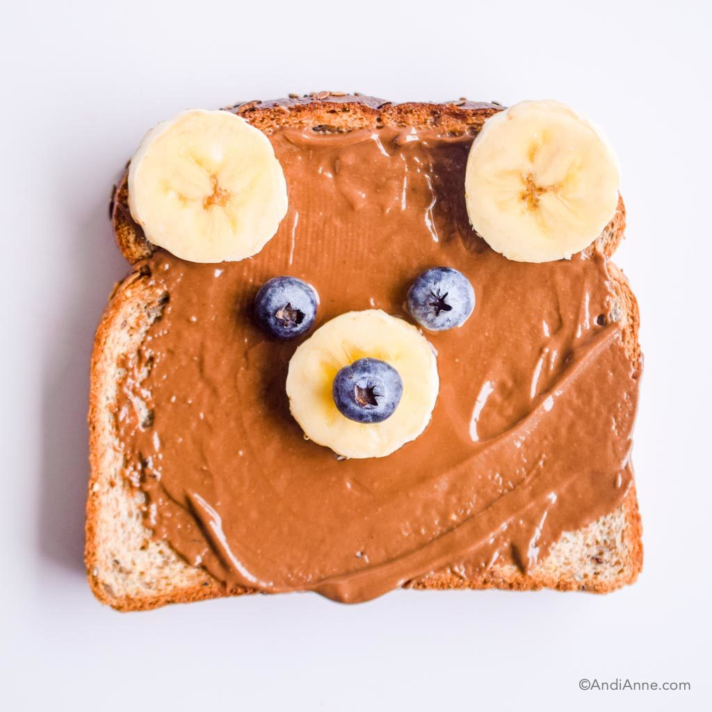 bear toast with chocolate nut butter spread, bananas and berries to make bear face