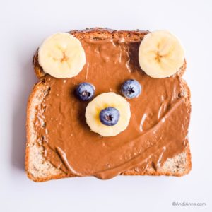 bear shape on toast using bananas for ears and nose, blueberries for eyes and top of nose