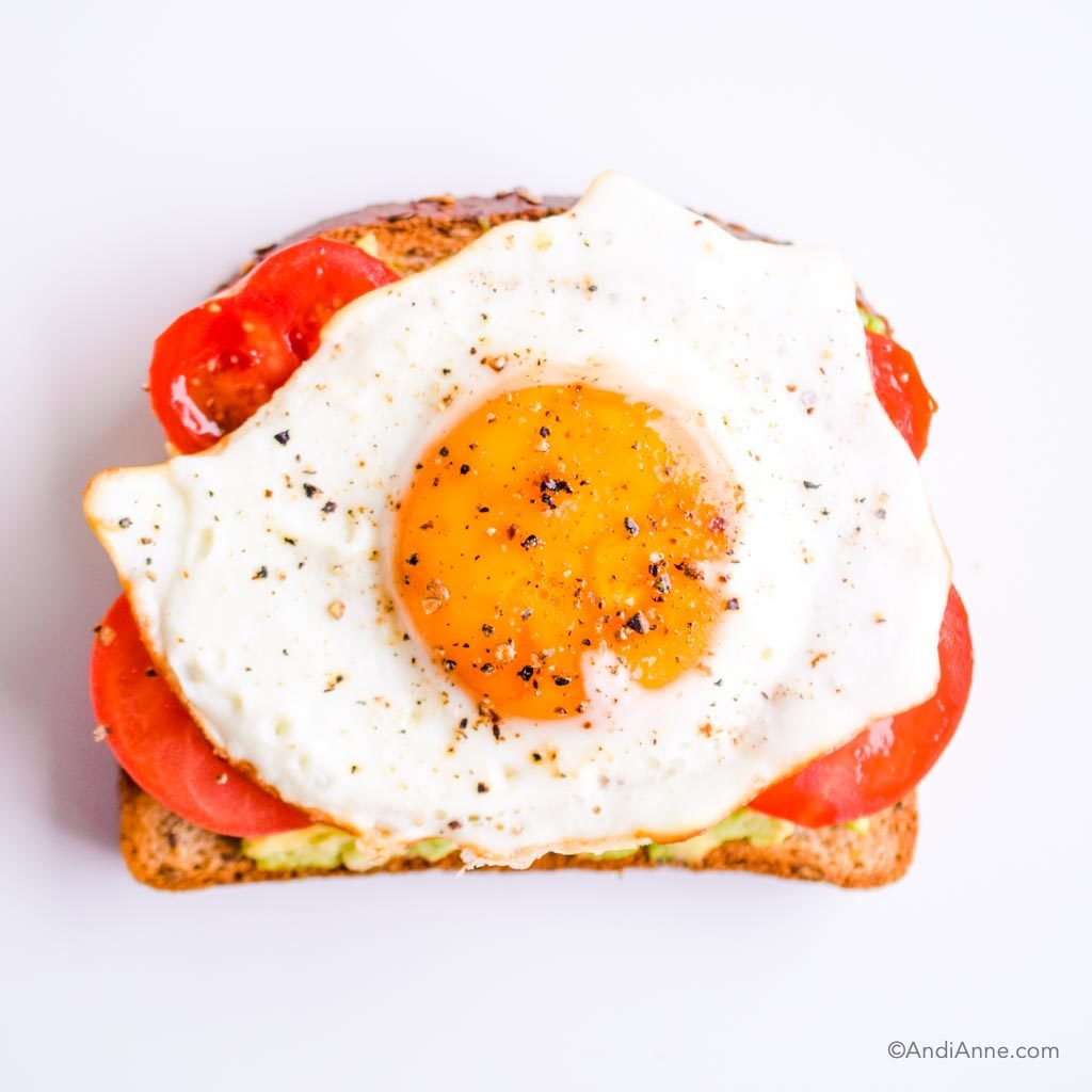 mashed avocado, sliced tomato and fried egg with salt and pepper on piece of toast