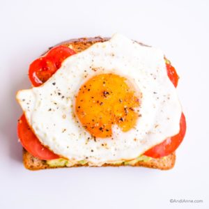 mashed avocado on toast. Topped with sliced tomato and a fried egg