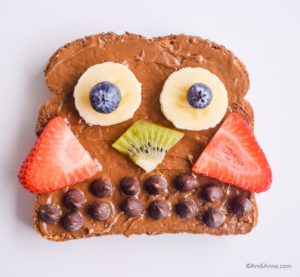owl shaped toast with nut butter spread. Berries and chocolate chips used to create owl shape