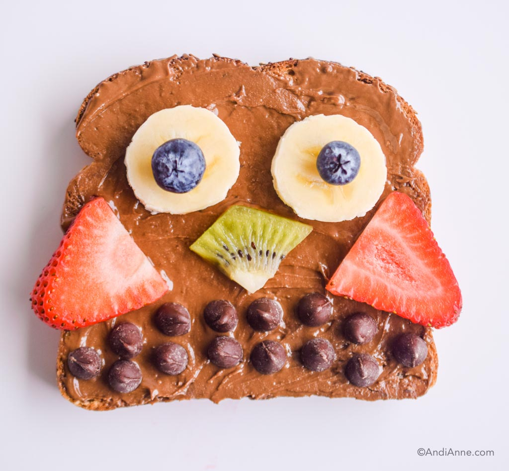 chocolate nut butter on toast with fresh berries and chocolate chips to form an owl shape