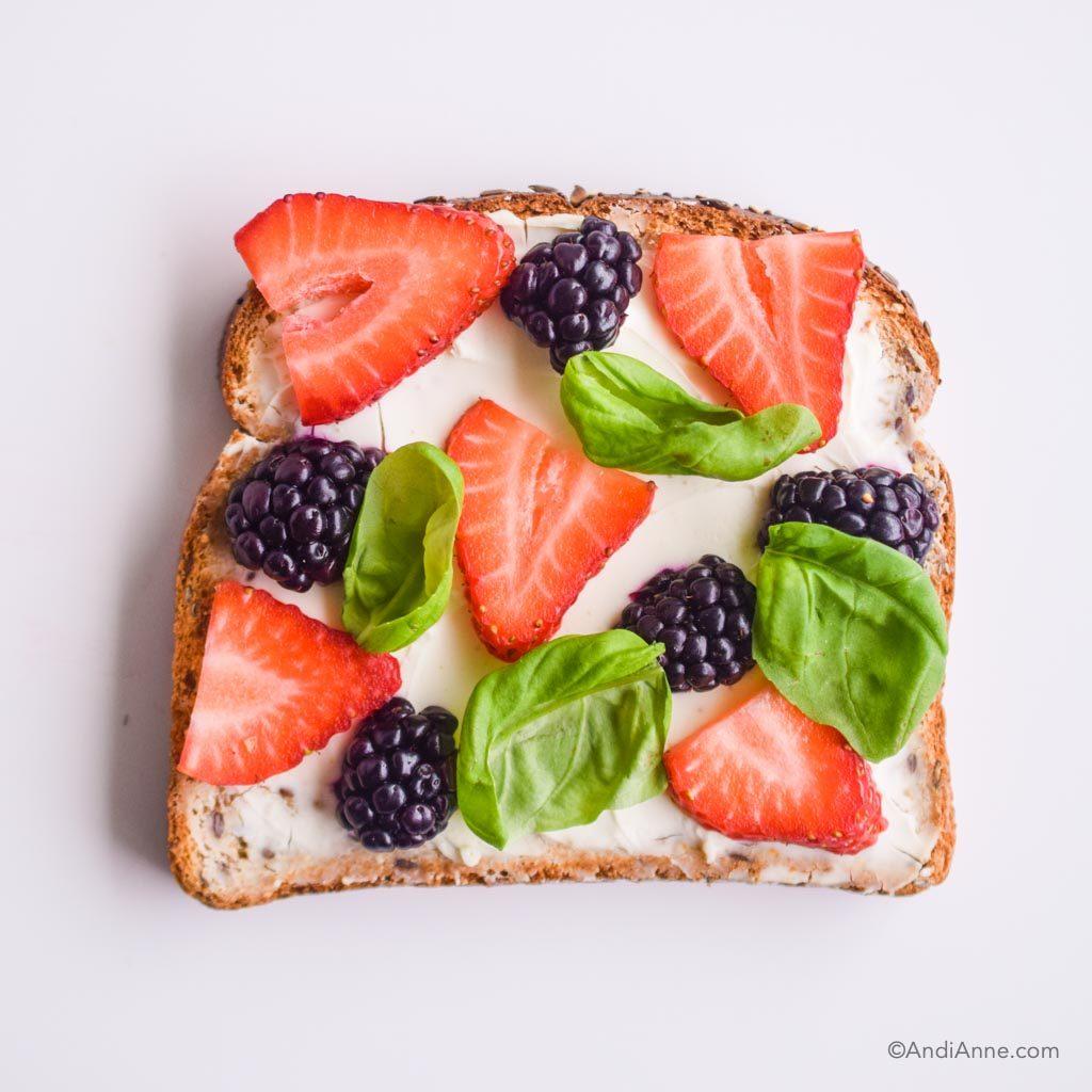 cream cheese toast with fresh sliced strawberries, sliced blackberries, and fresh basil