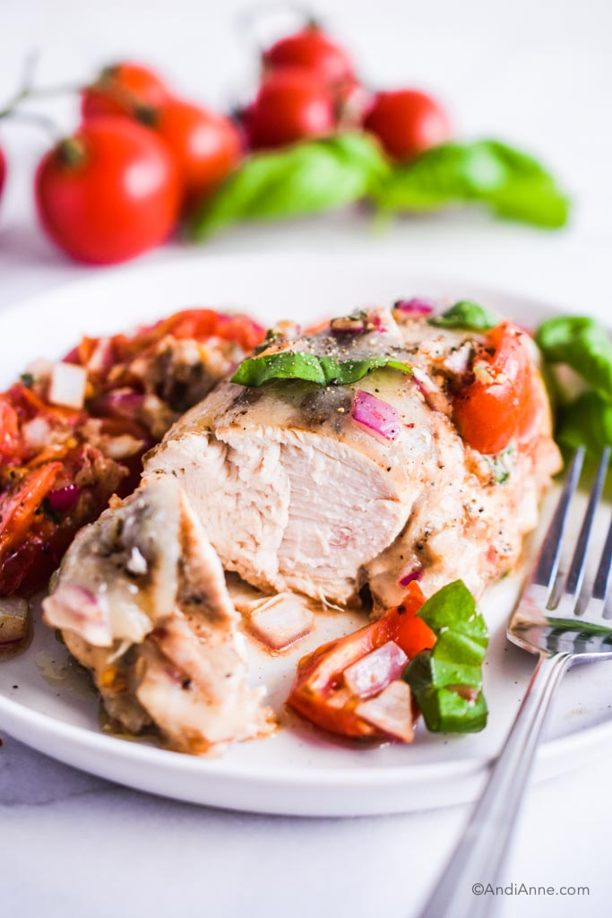 Chopped open chicken breast on plate with fork and tomatoes in background.