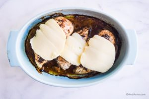 slices of mozzarella cheese on chicken breasts in blue oval baking dish