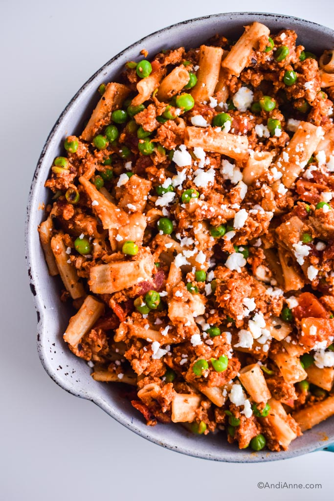 rigatoni, ground chicken and peas in a skillet with feta cheese sprinkled on top
