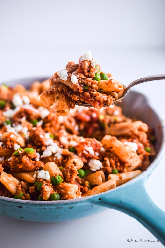 spoon holding rigatoni ground chicken with peas above the blue skillet