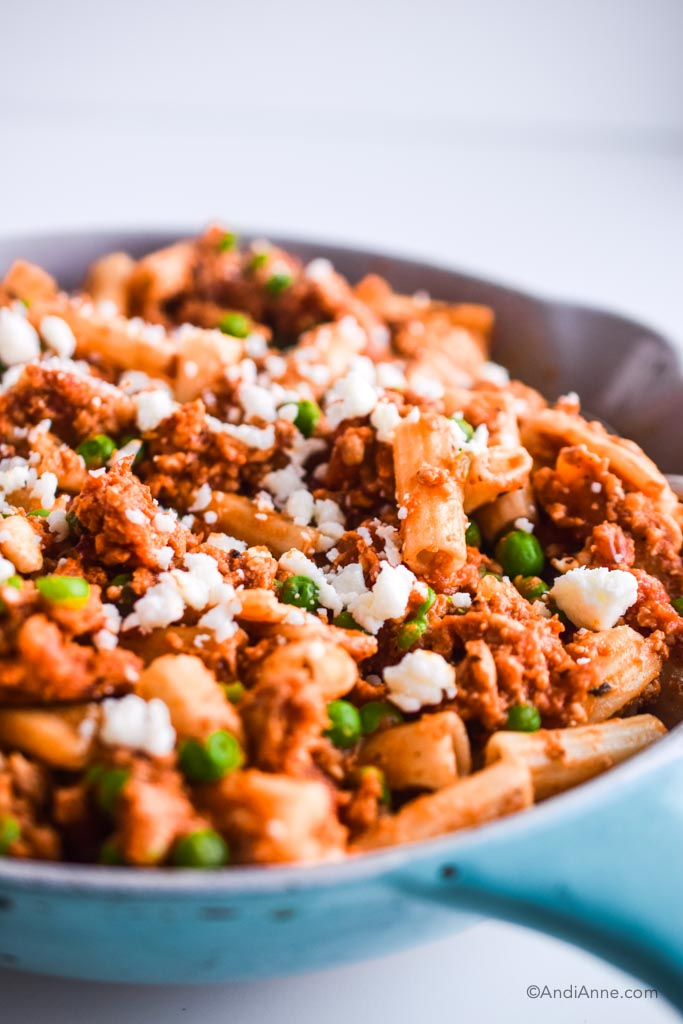 angle shot of rigatoni ground chicken  with peas and feta cheese in blue and white skillet