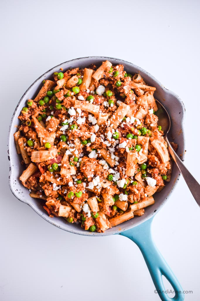 rigatoni, ground chicken peas and feta cheese in a blue and white skillet with silver spoon