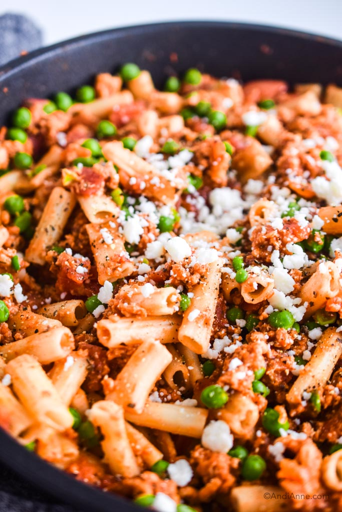 close up of rigatoni ground chicken and peas sprinkled with feta cheese