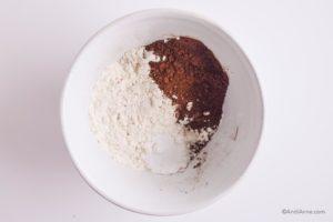 flour, cacao powder, baking soda and salt in a white bowl