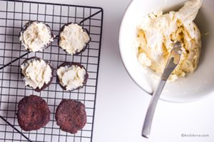 spreading cream cheese icing from a white bowl onto chocolate cookies with a butter knife