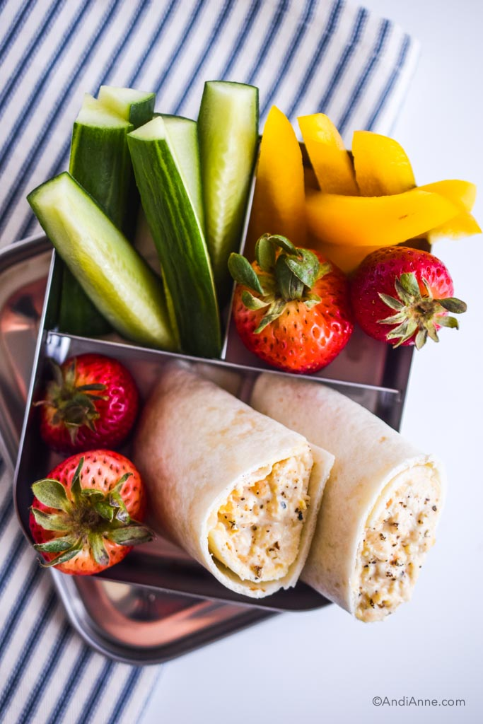 mashed chickpea wrap kids lunch in bento lunch box with sliced cucumber, sliced bell peppers, and strawberries. On a blue and white striped napkin.