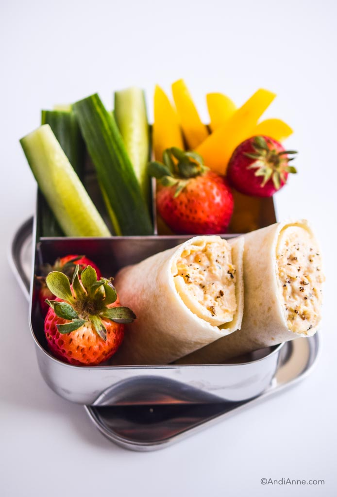 mashed chickpea wraps in kids steel bento lunch box with sliced cucumber, sliced bell peppers, and strawberries.