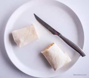 tortilla wrap folded and cut in half on white plate with silver knife