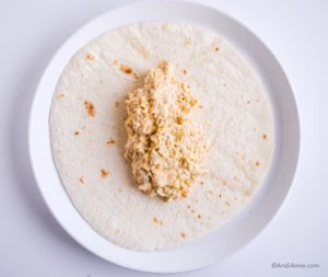 1 cup of mashed chickpea mixture in the center of flour tortilla on a white plate