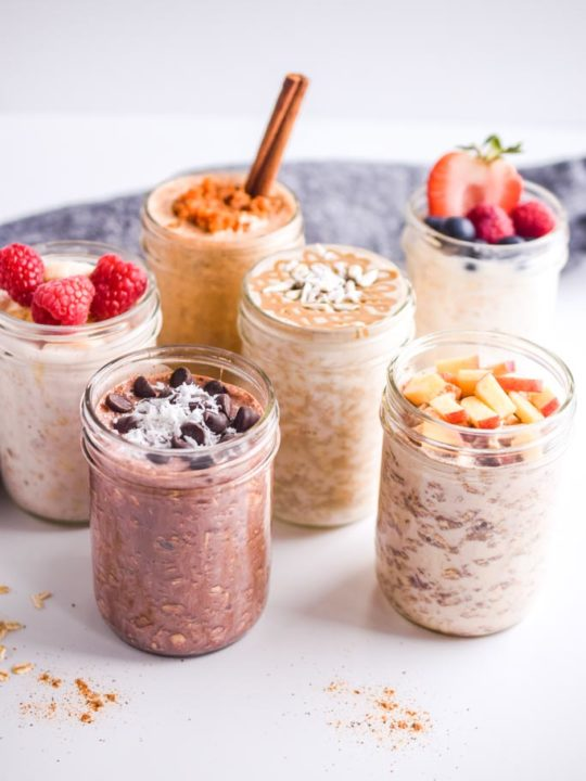 six overnight oats recipes in mason jars with fresh fruit toppings and dark napkin in background