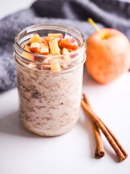 chopped apple on top of apple cinnamon overnight oats. Apple and cinnamon sticks in the background.