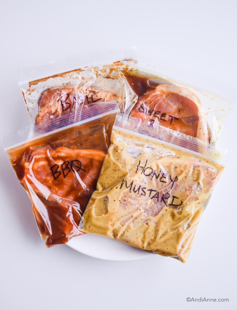 four healthy pork chop marinades in bags on a white plate