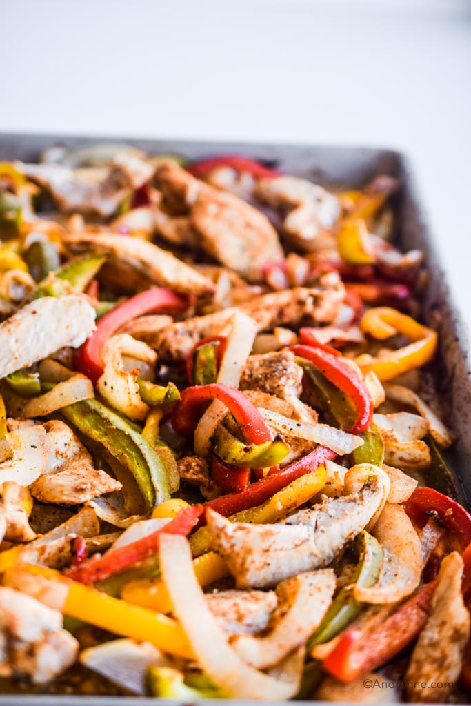 close up detail of chicken, sliced onion, sliced red, green and yellow bell peppers in a sheet pan