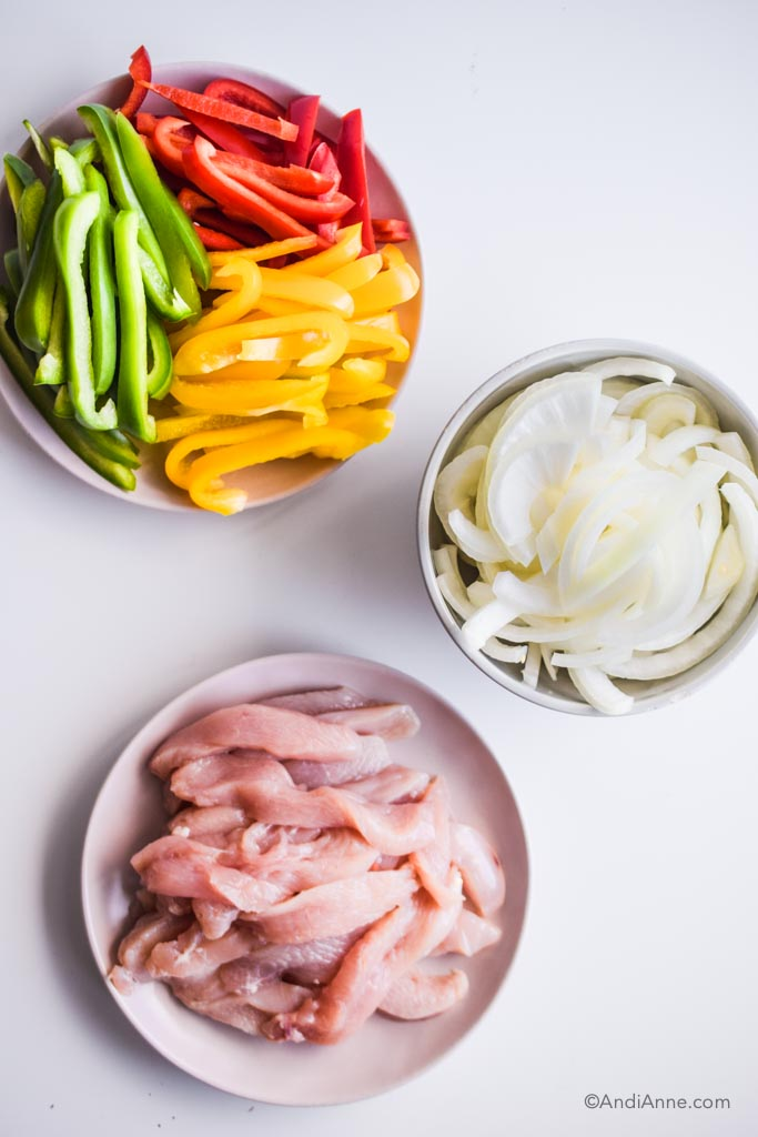 sliced red, green and yellow bell peppers on a plate. Sliced white onion in a grey bowl, and sliced raw chicken breast on a plate.