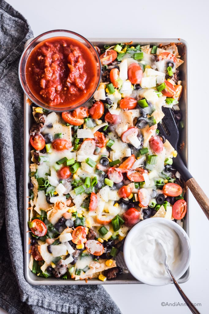 sheet pan nachos on baking sheet with bowl of salsa and bowl of sour cream. Spatula with wooden handle