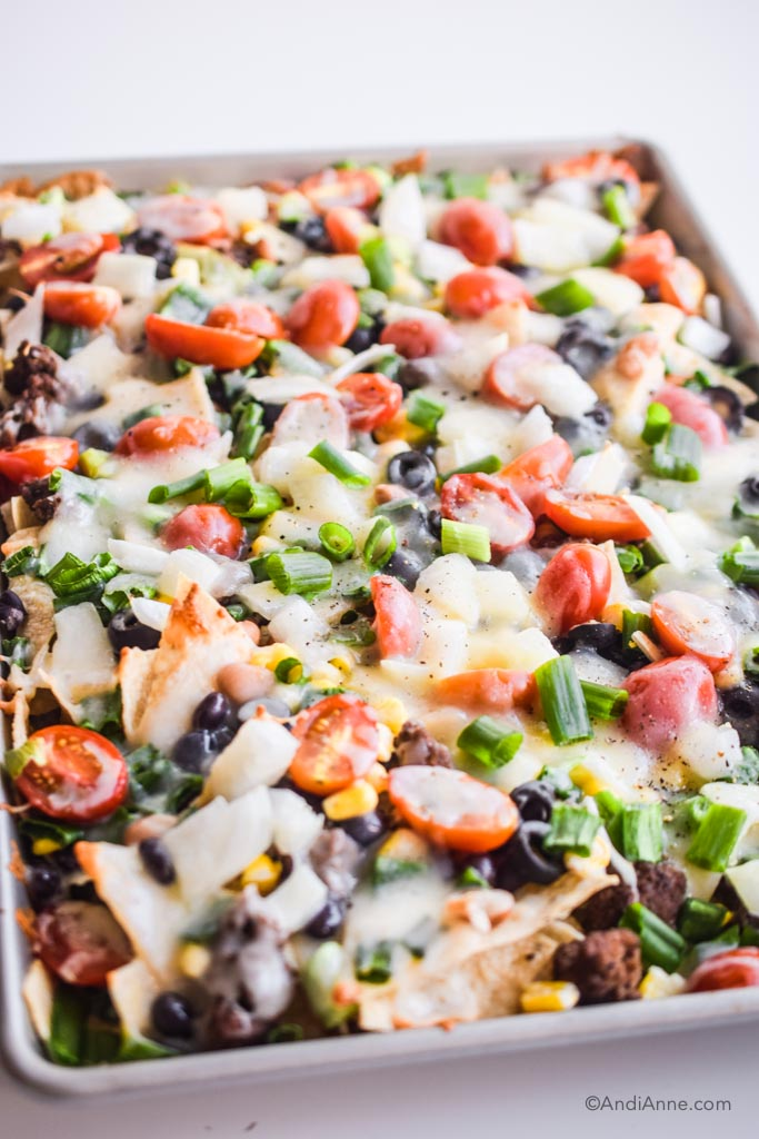 detail of melted cheese and all the veggies in the sheet pan nachos